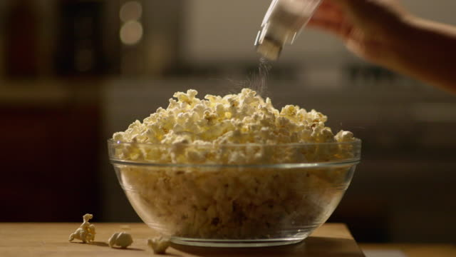 cu salt being pored onto popcorn - salt shaker stock videos and b-roll footage