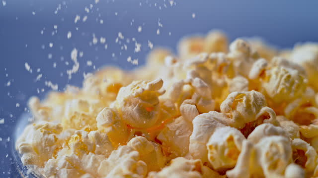 slo mo ld salt being sprinkled on top of popcorn - popcorn stock videos & royalty-free footage