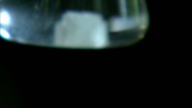 a salt crystal dissolves in a beaker. - dissolving stock videos & royalty-free footage