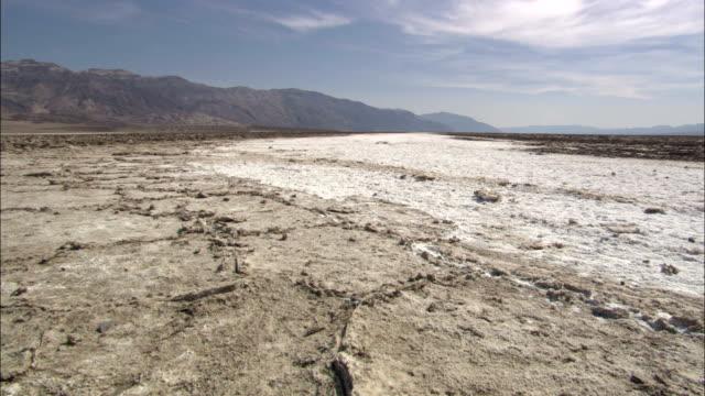salt deposits stretch toward death valley's mountainous horizon. - deserto mojave video stock e b–roll