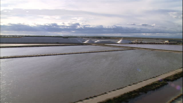 salt flats stretch across the landscape in provence, france. - camargue stock-videos und b-roll-filmmaterial