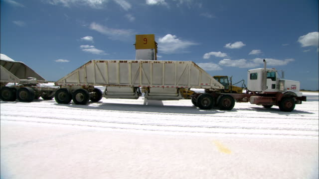 salt pours out of a front loader into a large trailer attached to a semi-truck. - mineral stock videos & royalty-free footage