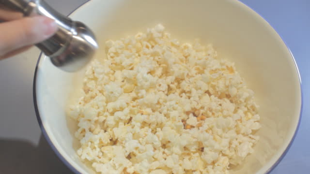 vídeos de stock, filmes e b-roll de salt sprinkled on popcorn in light blue bowl. - pipoca