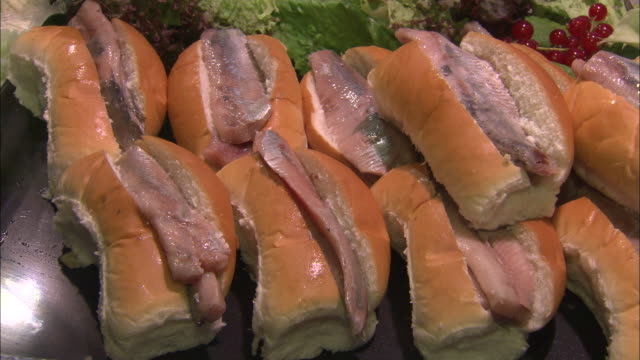 salted herring buns on display in amsterdam, the netherlands - tipo di panino video stock e b–roll