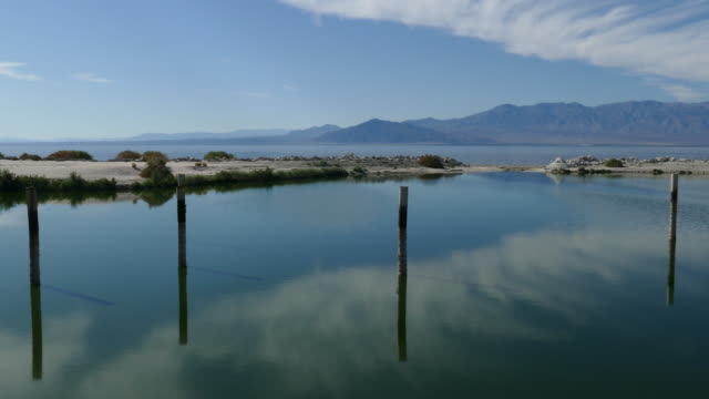 4k salton sea california morning looking out over the water with wispy clouds reflecting on the calm bay - faglia di sant'andrea video stock e b–roll