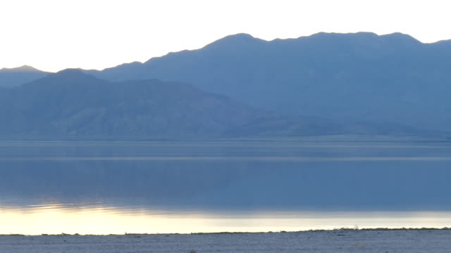 4k salton sea dusk grey silhouetted mountains reflecting pale colors in the rippling water - san andreas fault stock videos & royalty-free footage