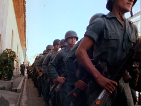 salvadorian civil war: government troops continue civilian killings; el salvador: ext troops lined up legs and rifles pull out drill move off to bv... - 中央アメリカ点の映像素材/bロール