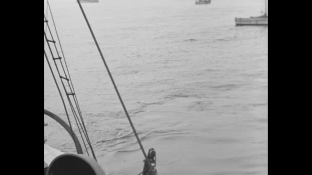 Salvage ship / VS crew at side of boat man climbs into diving apparatus three ships in distance diving bell lowered into water top of device with...