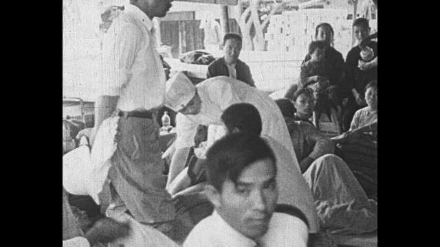 salvaged furniture on street / nurse attends to person in makeshift infirmary / women cooking food in large woks / note exact day not known - 1930~1939年点の映像素材/bロール