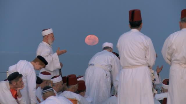 Samaritan pilgrims congregate before sunrise at Mount Gerizim with Moon at background/ West Bank city of Nablus,Samaria