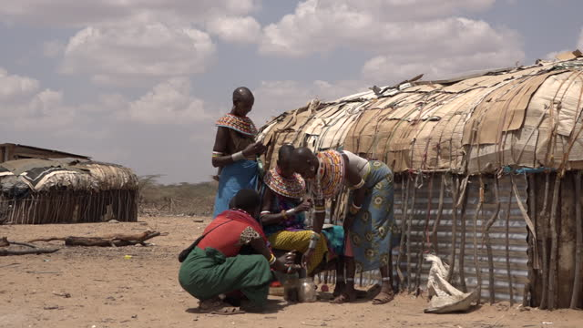 samburu people in front of huts on the sandy plains with acacia trees against the view on the mountains in wamba, kenya on july 13, 2019. - tropical tree stock videos & royalty-free footage