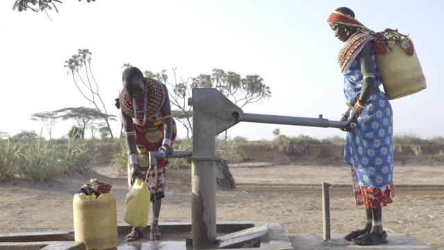 samburu women collecting freshwater from borehole. kenya, africa. - water pump stock videos & royalty-free footage