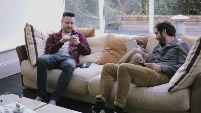 same sex couple family on the couch working with digital tablet and smart phone