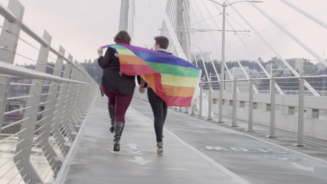 same sex couple holding hands under pride flag - teenage couple stock videos & royalty-free footage