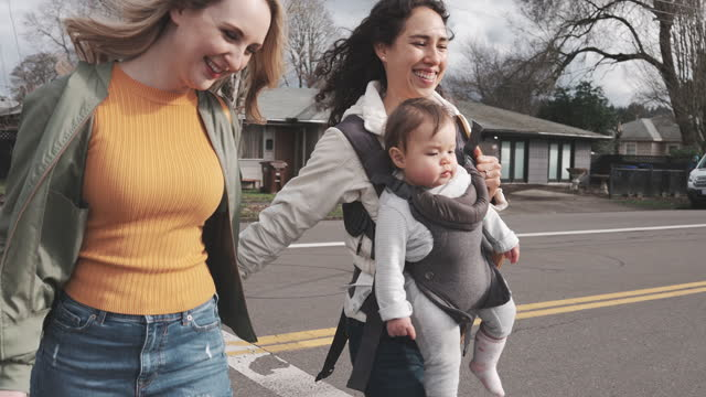same sex couple with cute baby girl walking across street - carrying stock videos & royalty-free footage