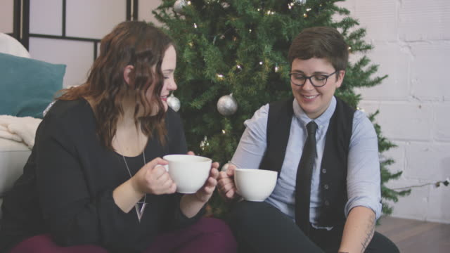 Same-Sex  Couple Sipping Hot Drinks by the Christmas Tree