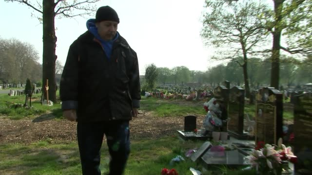 One year anniversary of death England London EXT Samer Sidhom along in graveyard crossing himself at Sami Sidom's grave and adjusting flowers Samer...