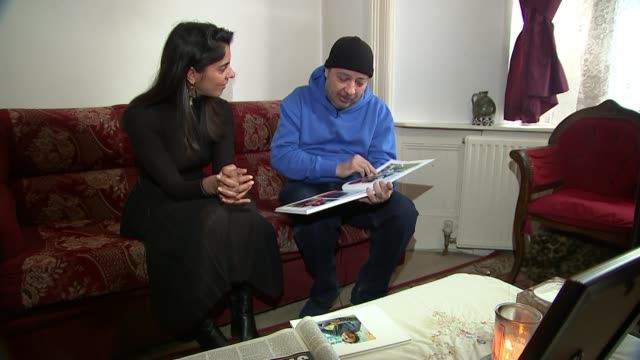 One year anniversary of death ENGLAND London INT Various shots of Samer Sidhom and reporter looking through photo album and chatting