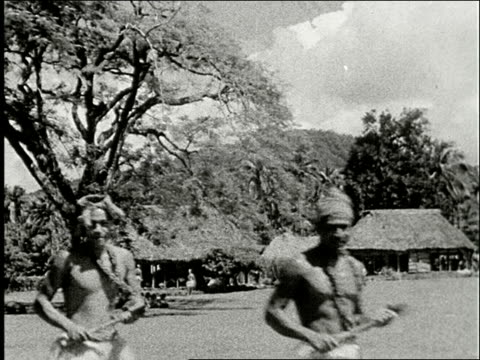 vídeos de stock e filmes b-roll de samoan village with round thatched houses / samoan men walk towards camera man sits next to wall of house / young bare chested boy holds small pig /... - samoa