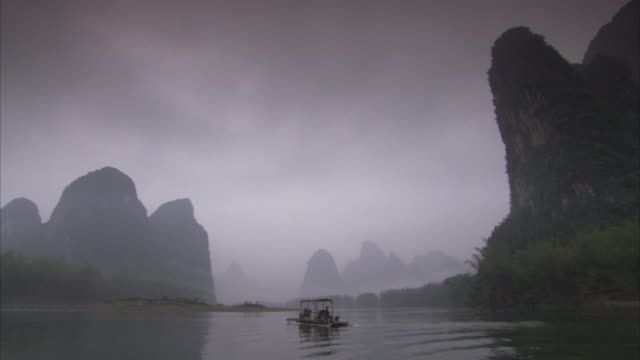 a sampan drifts through the mist in rural china. available in hd. - sampan stock videos & royalty-free footage
