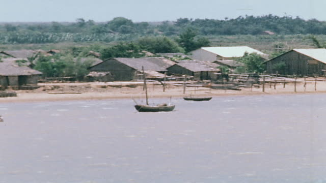 pan sampans anchored in shallow waters in front of shoreline village and waters of the mekong delta / vietnam - sampan stock videos & royalty-free footage