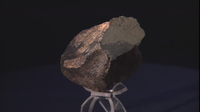 a sample of a meteorite rotates then stops against a black background. - payson stock videos & royalty-free footage