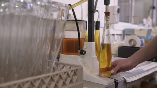 a sample of liquor is drawn from the copper pipes of the still and checked every half an hour for temperature control and alcohol content at the... - distillery still stock videos and b-roll footage