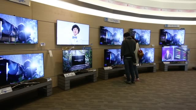 samsung electronics co. galaxy advertisement stands in gwanghwamun square in seoul, south korea, on tuesday, oct. 22 a customer tries out a samsung... - south korea couple stock videos & royalty-free footage