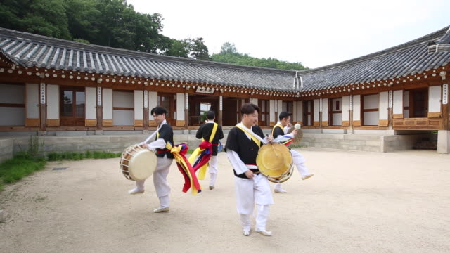 stockvideo's en b-roll-footage met samulnori (a genre of percussion music originating in korea) team playing instruments  in a courtyard of korean-style house - korea