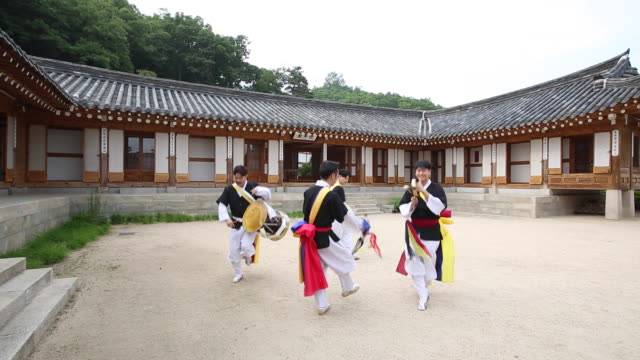 Samulnori (a genre of percussion music originating in Korea) team playing instruments  in a courtyard of Korean-style house