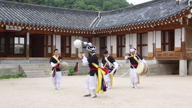 samulnori (a genre of percussion music originating in korea) team playing instruments  in a courtyard of korean-style house - 韓国点の映像素材/bロール