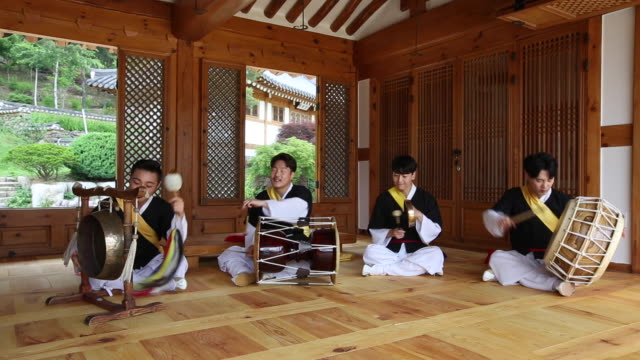 vídeos y material grabado en eventos de stock de samulnori (a genre of percussion music originating in korea) team playing instruments in korean-style house - corea