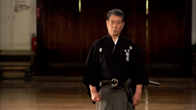 A Samurai instructor demonstrates the removal of a sword from a sheath. Available in HD.