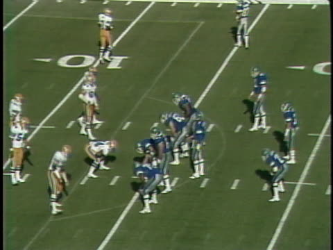 1984 MS San Antonio Gunslingers in huddle/ ball is snapped and Gunslingers' quarterback Rick Neuheisel throwing completed pass to Marcus Bonner in game against Oakland Invaders/ Invaders tackle Bonner and pile on top/ San Antonio, Texas