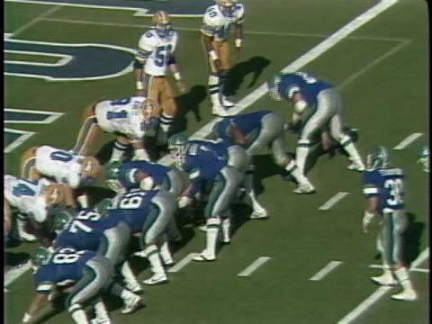 1984 ms san antonio gunslingers in huddle/ ball is snapped passed to al penn-white for play up the middle/ oakland invaders pile onto penn-white, who climbs out of pile and runs off field, celebrating completed play/ san antonio, texas - menschlicher arm stock-videos und b-roll-filmmaterial