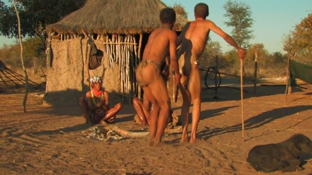 vídeos y material grabado en eventos de stock de san bushmen dance and clap outside a hut in namibia. available in hd. - techo de paja