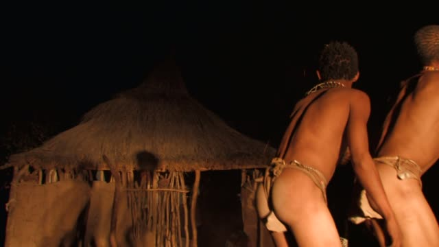 San bushmen dance around a campfire at night in Namibia. Available in HD.