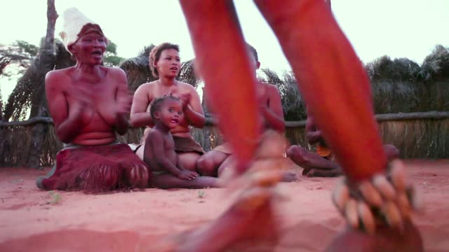 San Bushmen from the Khomani San community perform traditional dances around a fire in the Southern Kalahari Desert on October 15 2009 in the...