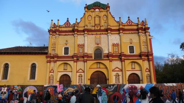 san cristóbal de las casas,san cristobal de las casas cathedral façade, with locals, vendors and a colorful fence. - chiapas stock-videos und b-roll-filmmaterial