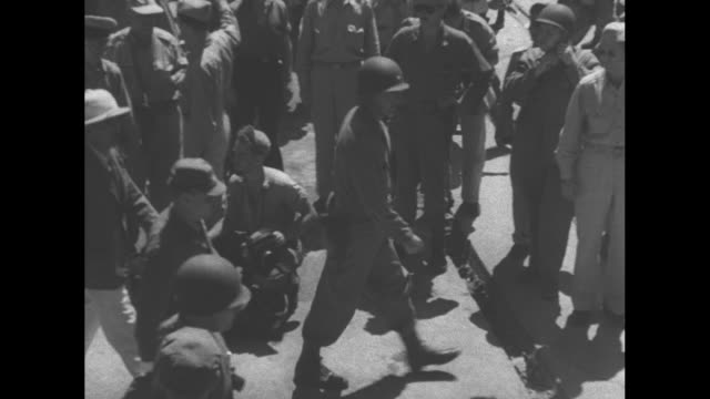 USS San Diego at wrecked Japanese dock during World War II / officers disembarking down gangplank / Japanese military men coming to greet Americans /...