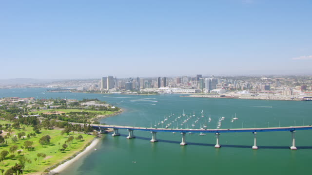 WS AERIAL POV San Diego Bay bridge and boats with Coronado Island in foreground and downtown in background / San Diego, California, United States