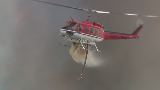 san diego, ca, u.s. - fire engines and a helicopter extinguishing the valley fire on wednesday, september 9, 2020. - kalifornien stock-videos und b-roll-filmmaterial