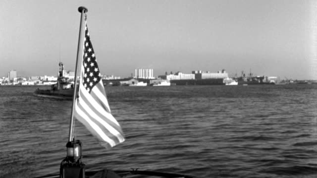 vidéos et rushes de dx - san diego harbor - from stern of second submarine - flag waving f.g. - submarine starts through across b.g. - b&w. - aller tranquillement