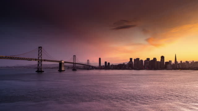 san francisco bay bridge and city sunset - time lapse - back lit video stock e b–roll