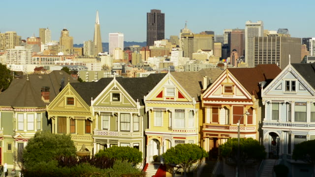 stockvideo's en b-roll-footage met san francisco california painted ladies victorian homes and city in background at alamo square at hayes street and steiner street - stadswoning