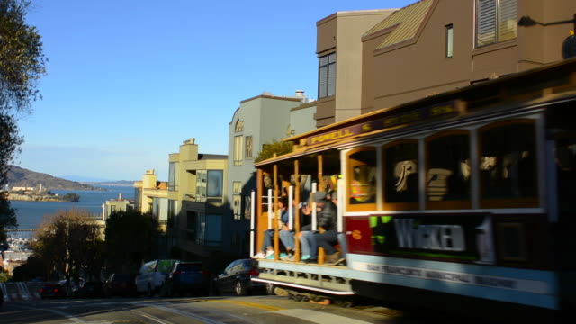 stockvideo's en b-roll-footage met san francisco california powell and hyde street cable car moving with passengers and tourists in traditional trolly transportation with alcatraz in background - kabelwagen