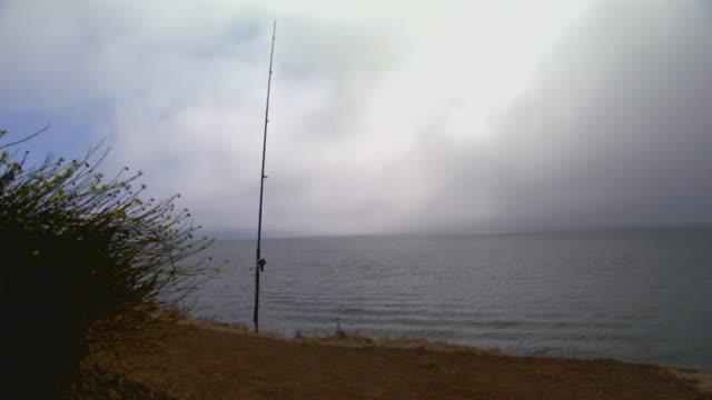 vídeos y material grabado en eventos de stock de san francisco, californiafishing pole on ocean cliff - caña de pescar
