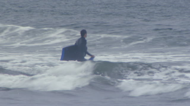 san francisco, californiayoung man wading out into water to use his boogey board - northern california stock videos & royalty-free footage