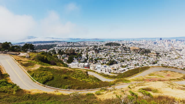 t/l san francisco city scape from twin peaks with rolling fog - 山間道路点の映像素材/bロール
