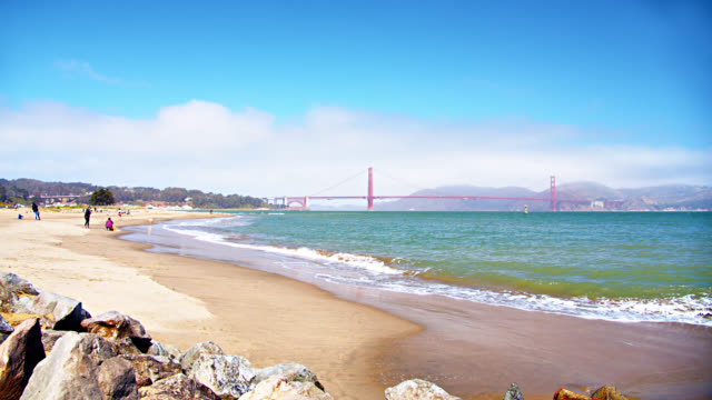 vídeos de stock, filmes e b-roll de san francisco golden gate bridge from a distance. sandy beach. rocks. mountains. - forma da água